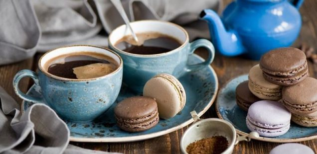Blue teapot with 2 cups sharing a saucer, cookies, and a crumpled napkin